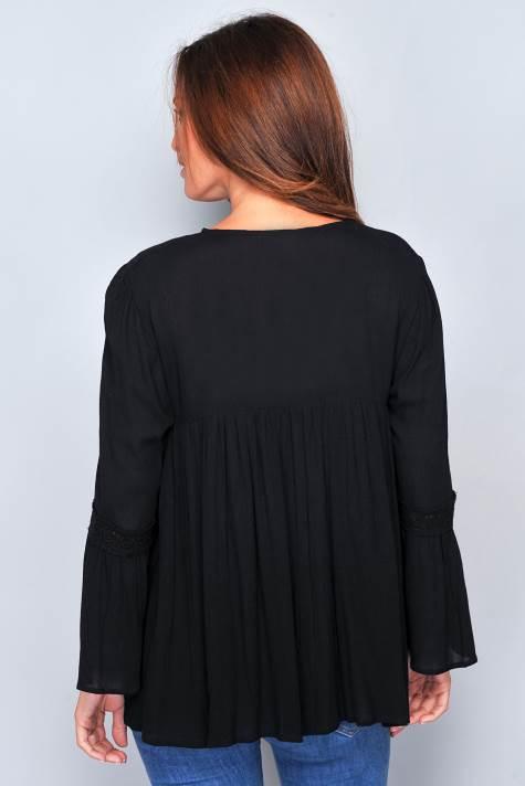 blusa negra con bordados en tonos suaves. Cuello con botones. Manga con volante