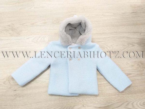 chaqueta de punto azul con pelito en el gorro gris brillante.