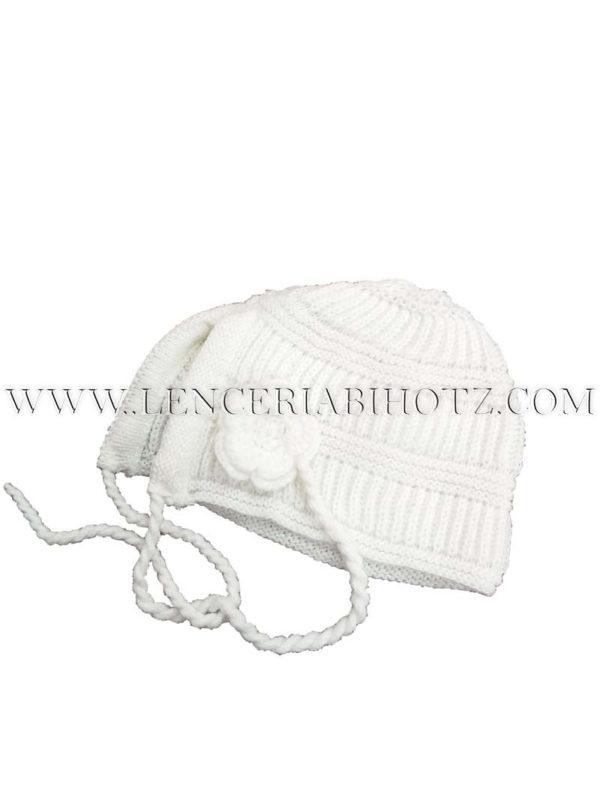 gorro bebe blanco de punto con cordones y abertura. Roseta en un lateral